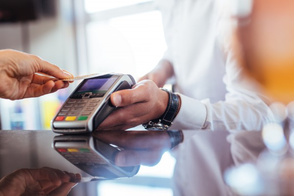 Hand of customer paying with contactless credit card with NFC technology. Bartender with a credit card reader machine at bar counter with female holding credit card. Focus on hands.; Shutterstock ID 744970960